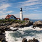 New England lighthouse with waves crashing on rocky shore